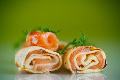 Rolls of thin pancakes with salted red fish Royalty Free Stock Image