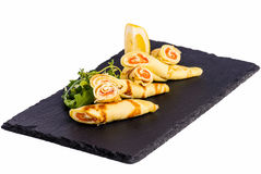 Rolls of thin pancakes with smoked salmonon stone. Rolls of thin pancakes with smoked salmon, cream cheese with rocket on stone on white Royalty Free Stock Photo