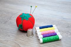 Rolls of thread with an out of focus pin cushion shaped as a red tomato and a thimble. On a wooden background stock photo