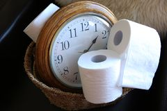 Rolls of toilet paper on the background of the old clock stock images