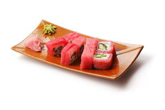 Rolls with tuna, crabmeat and onion. In brown squared plate over white background Royalty Free Stock Photography