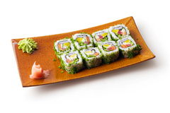 Rolls with tuna, salmon, cheese and cucumber. In brown squared plate over white background Stock Photos