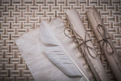 Rolls of vintage paper clean sheet feather on wicker mat Stock Photography