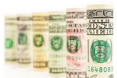 Rolls von amerikanischen Dollarbanknoten in einer Reihe Lizenzfreies Stockfoto