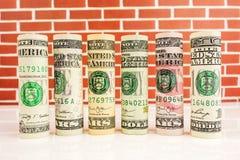 Rolls von amerikanischen Dollarbanknoten in einer Reihe Stockbilder