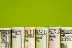 Rolls von amerikanischen Dollarbanknoten in einer Reihe Lizenzfreie Stockbilder