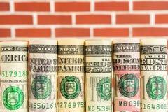 Rolls von amerikanischen Dollarbanknoten in einer Reihe Stockbild