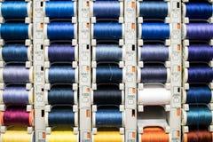 Rolls von Baumwolle benutzt für das Nähen Farbige Spulen des Nähgarns herausgestellt Lizenzfreies Stockfoto