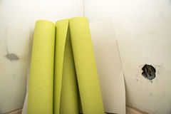 Rolls of wallpaper by plastered wall Stock Photos