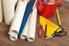 Rolls of wallpapers and various tools for wallpapering. Stock Image
