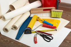 Rolls of wallpapers and various tools for wallpapering. Stock Images