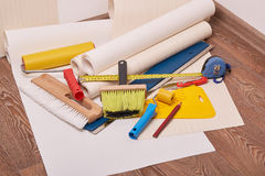 Rolls of wallpapers and various tools for wallpapering. Stock Photos