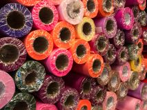 Rolls of wrapping paper in red, purple, green, burgundy, orange and pink stock photo