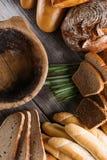 Rolls y panes en la tabla de madera con el cuenco de madera, el fondo para la panadería o el mercado Foto de archivo