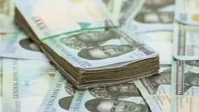 Rolls y paquetes de monedas locales del efectivo del naira en un montón de la pirámide fotografía de archivo