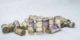 Rolls y paquetes de monedas locales del efectivo del naira en un montón de la pirámide imagen de archivo libre de regalías