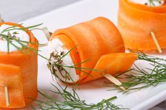 Rolls of young carrots with cottage cheese macro Stock Photos