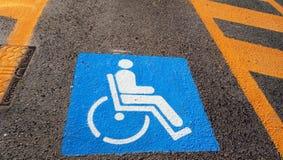 Rollstuhl-Handikap-Zeichen auf dunklem Asphaltstraße-Straßenhintergrundhandikap-Parkplatz stockbilder
