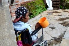 Rollstuhlbettler, der suchende Almosen des Schöpflöffels an den Kirchentor-Portalruinen hält Stockfotografie