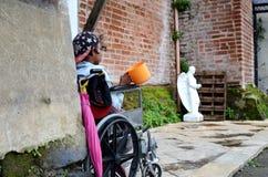 Rollstuhlbettler, der suchende Almosen des Schöpflöffels an den Kirchentor-Portalruinen hält Lizenzfreies Stockfoto