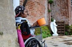 Rollstuhlbettler, der suchende Almosen des Schöpflöffels an den Kirchentor-Portalruinen hält Lizenzfreies Stockbild