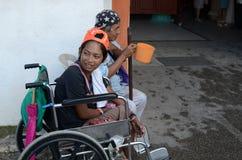 Rollstuhlbettler, der suchende Almosen des Schöpflöffels an den Kirchentor-Portalruinen hält Stockbild