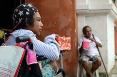 Rollstuhlbettler, der suchende Almosen der Weihnachtsgeschenkbox am Kirchentorportal hält Stockfotos
