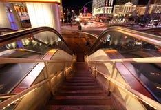 Rolltreppe und Treppenhaus unten mit unscharfem Verkehr und Leuchten Lizenzfreie Stockbilder