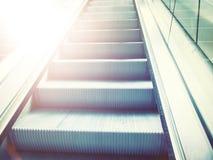 Rolltreppenschritte mit Sonnenaufflackern Lizenzfreie Stockbilder