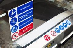 Rolltreppensicherheitszeichensymbole schließen oben und simsen auf Glas an der Spitze des elektrischen Aufzugs stockfoto