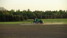 Rolnego ciągnika opryskiwanie nawozi pszenicznego pole z natryskownicą od herbicydu zbiory