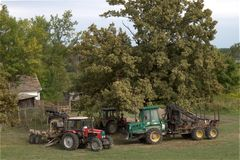 Rolnego ciągnika pojazdy pod drzewem przy lasu gospodarstwa rolnego domem Zdjęcia Royalty Free