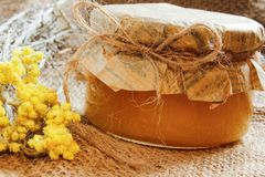 Rolnictwo Bank z miodem z kolorów żółtych suchymi kwiatami na burlap Boczny widok Zdjęcie Stock