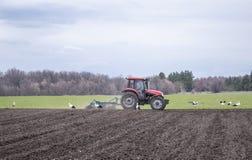 Rolnicy przygotowywa ziemi i fertilizingThe ci?gnika obchodz? si? ziemi? Rolnicy przygotowywaj? ziemi? dla sia? ziarna obraz stock