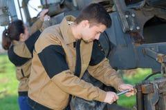 Rolniczy mechanicy sprawdza ciągnika warunek przed zbierać Zdjęcie Stock