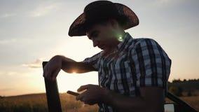 Rolnik jest ubranym kapelusz przy zmierzchem i pracuje na smarphone Komunikacja z klientami interesy nowoczesnego zbiory wideo