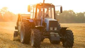 Rolnik na ciągnikowym zbiera polu przy wieczór zdjęcia royalty free