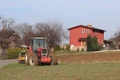 Rolnik na czerwonym ciągniku z ikrzakiem sia adrę w zaoranej ziemi w intymnym polu w wioska terenie Mechanizacja wiosna Fotografia Royalty Free