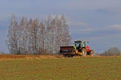 Rolnik na czerwonym ciągniku z ikrzakiem sia adrę w zaoranej ziemi w intymnym polu w wioska terenie Mechanizacja wiosna Obrazy Royalty Free