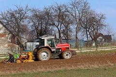 Rolnik na czerwonym ciągniku z ikrzakiem sia adrę w zaoranej ziemi w intymnym polu w wioska terenie Mechanizacja wiosna Fotografia Stock