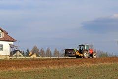 Rolnik na czerwonym ciągniku z ikrzakiem sia adrę w zaoranej ziemi w intymnym polu w wioska terenie Mechanizacja wiosna Obrazy Stock