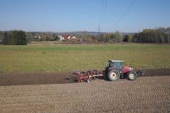 Rolnik na czerwonym ciągniku z ikrzakiem sia adrę w zaoranej ziemi w intymnym polu w wioska terenie Mechanizacja wiosna zdjęcie royalty free