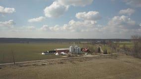 Rolnik na czerwonym ci?gniku z ikrzakiem sia adr? w zaoranej ziemi w intymnym polu w wioska terenie Mechanizacja wiosna zbiory