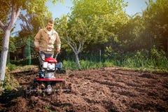 Rolnik orze ziemię z kultywatorem, przygotowywa je dla planti Obraz Stock