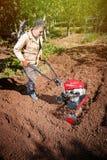 Rolnik orze ziemię z kultywatorem, przygotowywa je dla planti Obrazy Royalty Free
