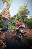 Rolnik orze ziemię z kultywatorem, przygotowywa je dla planti Zdjęcia Stock