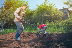 Rolnik orze ziemię z kultywatorem, przygotowywa je dla planti Zdjęcie Royalty Free