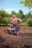 Rolnik orze ziemię z kultywatorem, przygotowywa je dla planti Fotografia Stock