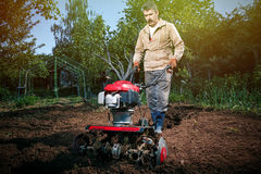 Rolnik orze ziemię z kultywatorem, przygotowywa je dla planti Obraz Royalty Free
