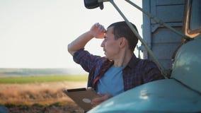 Rolnik używa cyfrowego pastylka komputer w kultywującym polu ciągnik w tle Pojęcie nowożytna technologia zbiory